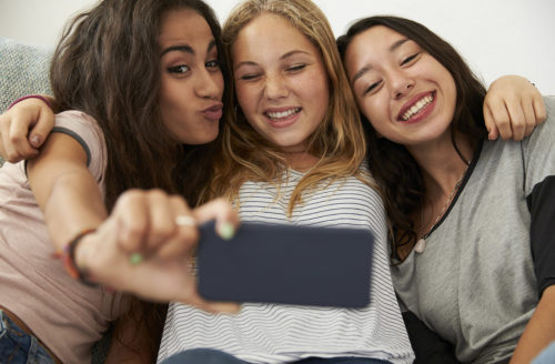 Drei Mädchen machen ein Selfie voneinander